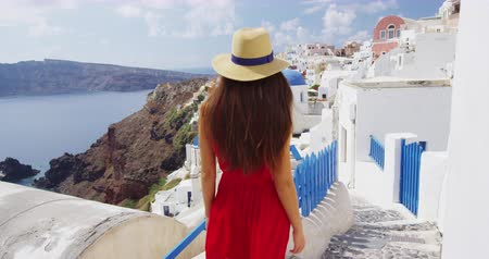 sunhat : Vacation -Tourist travel woman in Oia, Santorini, Greece. Happy young woman walking on stairs by famous blue dome church landmark destination. Beautiful girl in red dress on visiting the Greek island.