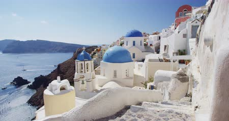 Киклады : Santorini Oia Blue Domed Church tourist attraction. Beautiful view of Mediterranean Sea and village of Oia. Scenic view of traditional white houses and blue domes on church. Greece, Europe