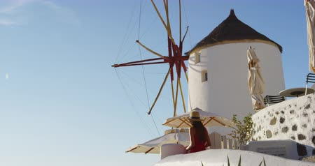 УВР : Santorini Famous Landmark And Tourist Attraction - Windmill In Oia Santorini. Tourist woman looking at view. Traditional Greek Islands architecture. Vacation in Greece, Europe. Стоковые видеозаписи