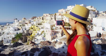 Санторини : Woman taking photos using smart phone in Oia, Santorini, Greece, Europe. Girl tourist sighseeing taking picture of famous tourist village of Oia on travel vacation holidays, RED EPIC SLOW MOTION