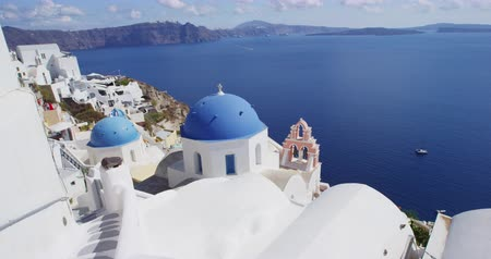 Киклады : Santorini Oia blue domes of church and caldera travel destination. Beautiful view of white typical village and Aegean Sea i. View of blue domed churches -famous tourist attraction in Greece.