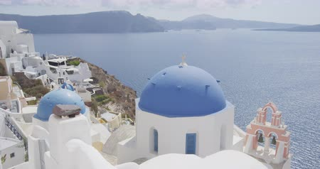 УВР : Santorini Oia village Blue Domed Church. Scenic view of traditional Cycladic white houses and blue domes. Beautiful view of Mediterranean Sea and village in Santorini. Famous travel tourist attraction Стоковые видеозаписи