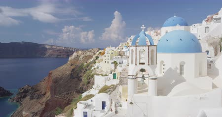 УВР : Santorini Oia village Blue Domed Church - Famous travel vacation destionation. Traditional Cycladic white houses and blue domes. Beautiful view of Mediterranean Sea and village in Santorini.