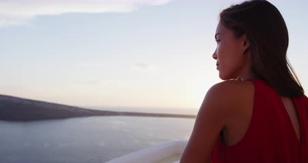 УВР : Beautiful woman enjoying the beautiful view of Aegean Sea during sunset. Female tourist is wearing red dress while standing at caldera. She is on her vacation in Santorini.