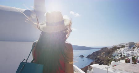 Санторини : Travel Vacation ion Europe. Happy tourist woman enjoying beautiful view of village Oia and sea. Young female is wearing sun hat enjoying her summer vacation in Greek Islands, Santorini, Greece