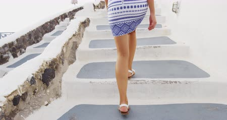 hostující : Woman legs walking close up on stairs outside. Travel tourist woman walking on in Oia, Santorini. Lady visiting famous island destination in Greece, Europe. SLOW MOTION,
