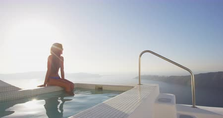 джакузи : Travel Vacation Luxury Woman Sunbathing Relaxing By Spa Swimming Pool Enjoying Sunset. Relaxing woman watching sunset over sea from resort on Santorini, Greek Islands, Greece, Europe. Стоковые видеозаписи