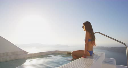 джакузи : Luxury travel happy woman in bikini relaxing at the edge of swimming pool. Young Asian female is watching beautiful view of sunset. She is enjoying her vacation by sea. Santorini, Greece. Стоковые видеозаписи