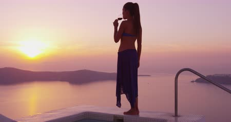 джакузи : Travel Vacation Luxury lifestyle woman drinking glass of red wine walking at private swimming pool. Woman enjoying drink by sea during sunset. Female model on vacation holidays on Santorini, Greece.