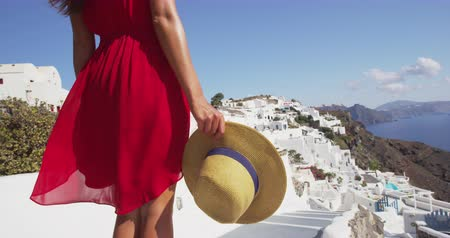 УВР : Travel in Europe. Santorini travel vacation tourist walking looking at caldera view and Aegean Sea. Woman visiting travel destination wearing red dress in Oia, Santorini, Greek Islands, Greece.