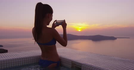 джакузи : Europe travel woman in bikini in pool spa by taking photo using phone of sunset view on vacation holidays. Model in swimming pool. Asian girl enjoying vacation on Santorini, Greece