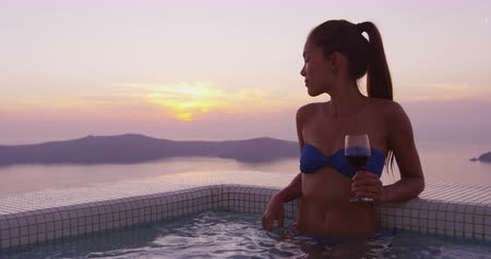 Санторини : Europe travel woman in bikini in pool spa by amazing sunset view on vacation holidays. Model drinking glass of red wine at in swimming pool. Asian female is enjoying her vacation on Santorini, Greece.
