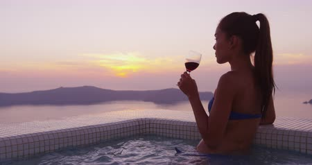 джакузи : Europe travel woman in bikini in pool spa by amazing sunset view. Model drinking glass of red wine at the edge of swimming pool. Asian girl enjoying her vacation on Santorini, Greece Стоковые видеозаписи