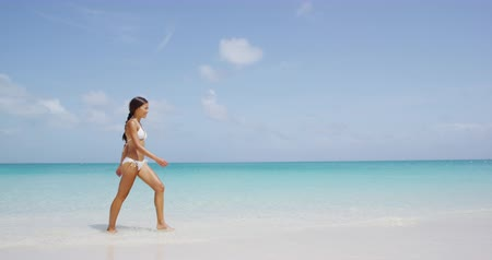 genç kız : Beach vacation travel woman relaxing in bikini walking on perfect tropical paradise Caribbean beach with turquoise ocean water during summer vacations holidays. Happy lifestyle Asian girl. SLOW MOTION