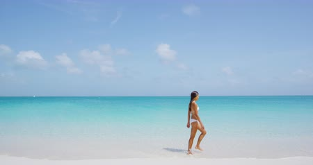 opalenizna : Vacation Travel Beach Life. Woman in bikini walking on perfect paradise beach with white sand and turquoise water. Beautiful multiracial model relaxing on summer vacation travel. SLOW MOTION STEADICAM