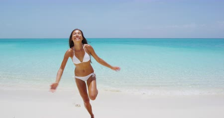 coming : Travel Vacation Woman Happy Enjoying Summer Beach Holidays Jumping Having Fun Running Out Of Water. Beautiful woman in white bikini.