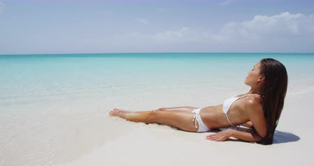 купаться : Beach body woman sun bathing on travel vacation. Sexy bikini body woman relaxing sun tanning lying down sunbathing on perfect paradise beach at tropical luxury destination in the Caribbean.
