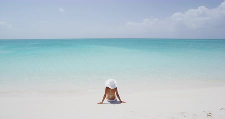 sunhat : Beach travel vacation holidays concept. Woman on white sand paradise beach. Rear view of female wearing bikini and sun hat while sunbathing
