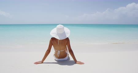 sunhat : Beach Sun travel vacation holidays concept. Woman woman on white sand paradise beach. Rear view of female wearing bikini and sun hat while sunbathing.