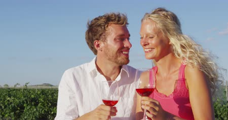 cheers : Wine drinking couple kissing romantic at vineyard in love on date. Woman and man in love drinking red or rose wine smiling happy flirting outside. Young Caucasian man and woman in love.