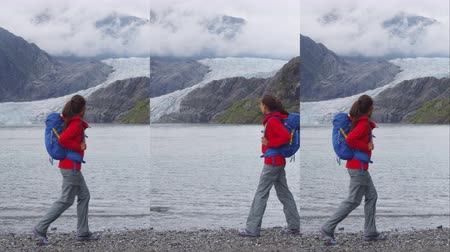függőleges : Tourist hiking woman in Alaska walking by Mendenhall Glacier landscape. Woman hiker on travel adventure trekking wearing backpack Stock mozgókép