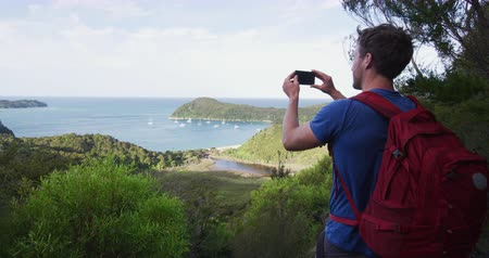 tramp : New Zealand travel man taking pictures with smart phone of the Anchorage in Abel Tasman National park, New Zealand vacation. Male backpacker tramping hiking on Abel Tasman Coast Track. SLOW MOTION.