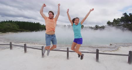 champagne pool : New Zealand happy tourist couple jumping happy having fun at famous attraction travel destination. Champagne pool, Waiotapu. Active geothermal area, in Taupo Volcanic Zone, Rotorua, New Zealand.
