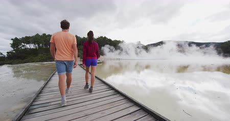 grão : New Zealand travel. Tourists couple at Champagne pool at Wai-O-Tapu pools Sacred Waters. Tourist attraction in Waiotapu, Rotorua, north island. Active geothermal area, Okataina Volcanic Centre, Taupo.