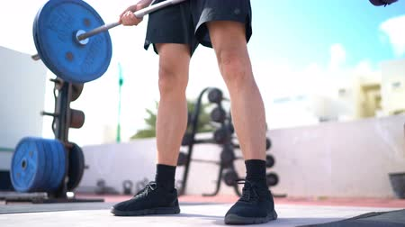 quads : Weightlifting fitness man bodybuilding or powerlifting at outdoor gym. Bodybuilder doing barbell weight workout deadlift with heavy bar.