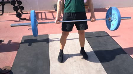 quads : Deadlift - Weightlifting fitness man bodybuilding or powerlifting at outdoors gym. Bodybuilder doing barbell weight workout deadlift with heavy bar.