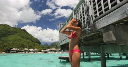hotel suite : Luxury travel destination bikini woman taking an outdoor shower at luxury resort hotel overwater bungalow in Tahiti. Vacations in paradise Asian girl showering after swim. Stock Footage