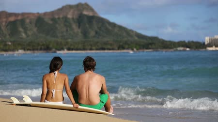 Оаху : Hawaii surfers relaxing on waikiki beach with surfboards looking at waves in Honolulu, Hawaii. Healthy active lifestyle fitness surfer couple at sunset with diamond head mountain in the background. Стоковые видеозаписи