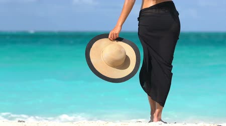 sunhat : Luxury travel woman in black bikini and sarong standing on beach. Sexy woman is enjoying wind on shore. Lady is holding sunhat during summer vacation by turquoise sea at beach resort.