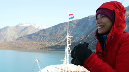 wieloryb : Alaska Glacier Bay Tourist looking at landscape using binoculars on cruise ship. Woman on vacation travel looking for wildlife enjoying cruising famous tourist destination. RED EPIC SLOW MOTION.