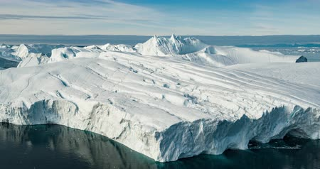 ilulissat : Iceberg aerial drone video - Global warming and climate change concept. Giant icebergs in Disko Bay on greenland in Ilulissat icefjord from melting glacier Sermeq Kujalleq Glacier, Jakobhavns Glacier.