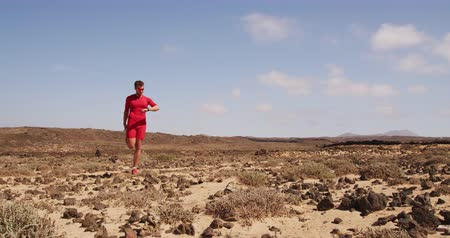 率 : Running man - male runner looking at fitness smartwatch while stretching. Fit man trail runner warming up doing stretches using smart watch heart rate monitor in desert nature landscape. SLOW MOTION.
