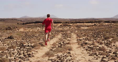 sprintel : Athlete running man - male runner. Sporty fit young man running fast on trail in desert training hard for fitness goals. Man running away from camera SLOW MOTION.