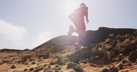 sprintel : Fitness running man living healthy active successful lifestyle. Trail runner in desert - male athlete running fast. Jumping sprinting legs and running shoes in SLOW MOTION. Shot on RED.