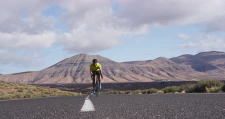 rowerzysta : Road biking cyclist man training on bike. Professional cycling athlete riding racing bicycle training for competition race on open road. SLOW MOTION shot on RED.
