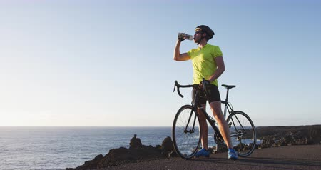 relaks : Energy sports drink - cyclist drinking from water bottle on rode bike training. Man biking taking break
