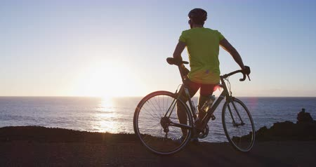 ciclista : Cyclist man relaxing on road bike looking at sunset and ocean after cycling biking training. Healthy active lifestyle sports fitness man resting on bike after exercise. SLOW MOTION shot on RED. Stock Footage