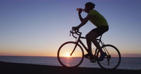 hydratace : Cyclist athlete man cycling biking training exercise and drinking water. Healthy active lifestyle sports fitness man exercising at sunset. SLOW MOTION RED Cinema Camera.