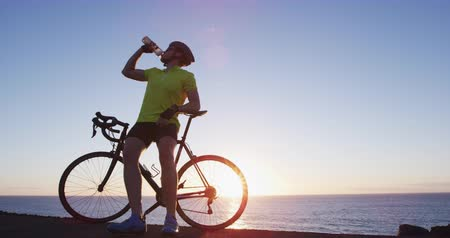 évad : Athlete cyclist man drinking water on road bike after intensive cycling biking training. Healthy active lifestyle sports fitness man resting on bike after exercise. SLOW MOTION shot on RED at sunset.