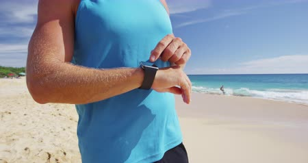 felnőtt : Athlete runner checking cardio on sports smartwatch jogging on beach outdoors. Running man wearing tech wearable device looking at watch during training workout. Stock mozgókép