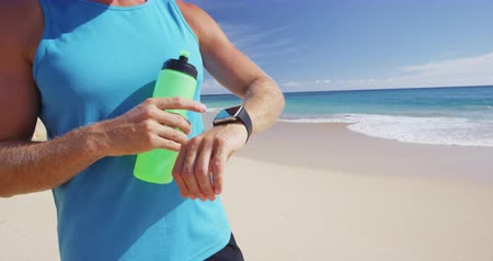 fitnes : Sports smartwatch - Athlete runner drinking water or energy sports drink from bottle checking fitness tracker on smartwatch exercising on beach. SLOW MOTION.