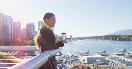 Ванкувер : Woman in Vancouver harbour downtown looking at view happy - businesswoman taking coffee break enjoying view of waterfront, skyline and seaplanes. Multicultural model. Young urban professional.