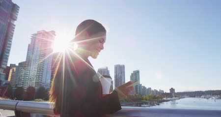 kanadský : Woman in Vancouver harbour downtown looking at phone - businesswoman in city - businesswoman taking coffee break enjoying coffee. Multicultural model. Young urban professional. SLow motion. Dostupné videozáznamy