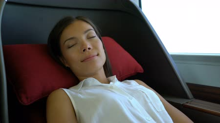 magánélet : Woman relaxing sleeping in comfortable first class seat in train during travel. Asian businesswoman commuter professional. Transport travel lifestyle.