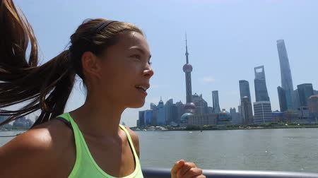 bund : Asian woman running in city of Shanghai, China on famous boardwalk with skyline. Urban city lifestyle. Active woman runner exercising outside jogging on the Bund. Action camera