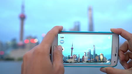 orientalne : Shanghai China travel in Asia. Tourist taking phone photo on the Bund in Shanghai city vacation using smartphone app for posting on social media. Focus change.